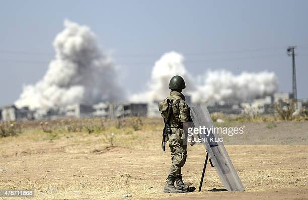 A picture taken from the Turkish side of the border in Suruc Sanliurfa province shows a Turkish solider standing as smoke rises from the Syrian town...