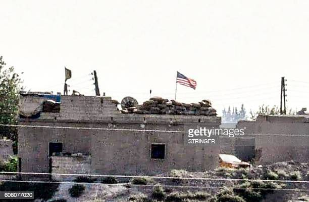 A picture taken from the Turkish side of the Syrian border in the Turkish town of Akcakale in Sanliurfa shows a US flag at the People's Protection...