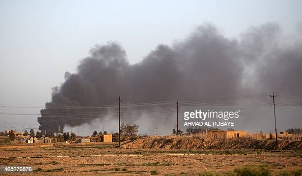 A picture taken from the village of Awja on the outskirts of the city of Tikrit on March 5 shows smoke rising from a location in the city of Tikrit...