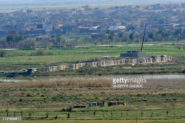 A picture taken from the village of Baghouz in the countryside of the eastern Syrian province of Deir Ezzor on March 20 shows a wall separating the...