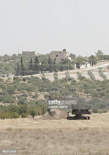 A picture taken from Turkey's Gaziantep province which has border with Jarabulus district of Syria's Aleppo province shows Daesh militants walk and...