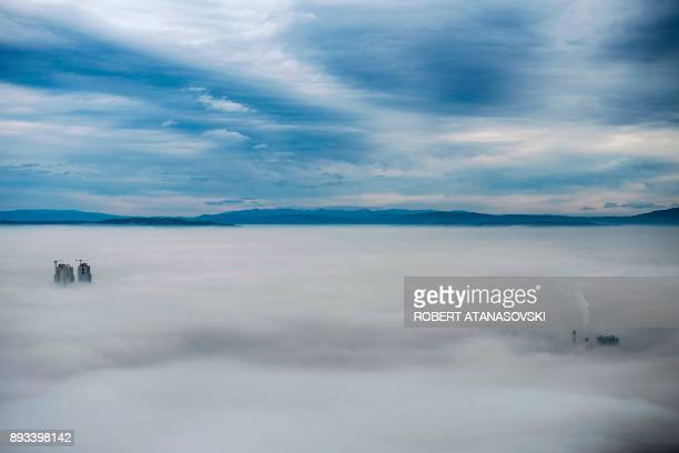 TOPSHOT A picture taken from Vodno Mountain shows some of the city's highest buildings and smoke rising from chimneys of a factory in an area with a...