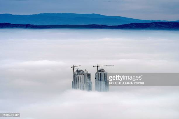 TOPSHOT A picture taken from Vodno Mountain shows the tops of some of the city's highest buildings above clouds in an area with a high level of air...