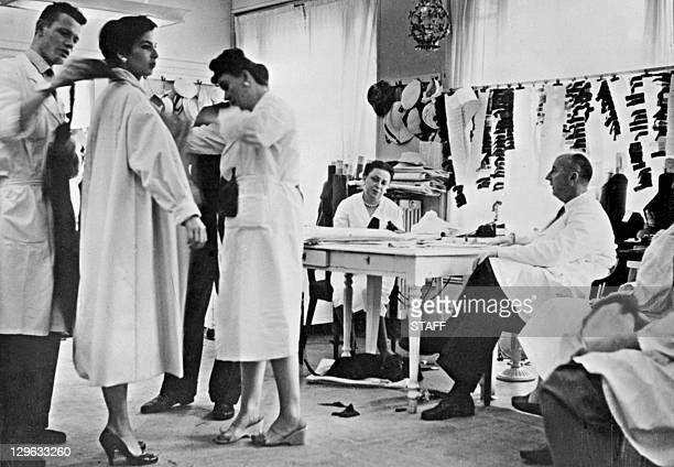 Picture taken in 1956 of French designer Christian Dior among his staff preparing a collection in his atelier in Paris