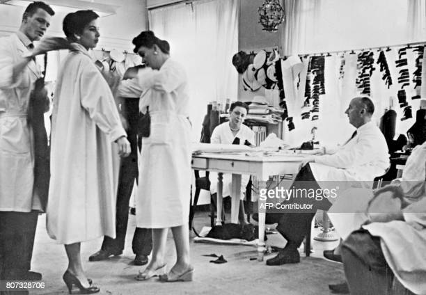 Picture taken in 1956 of French designer Christian Dior among his staff preparing a collection in his atelier in Paris / AFP PHOTO / STAFF