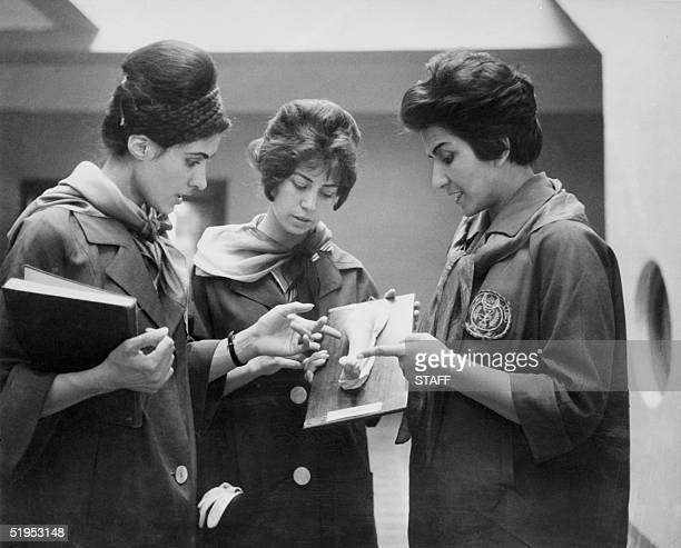 Picture taken in 1962 at the Faculty of Medecine in Kabul of two Afghan medicine students listening to their Professor as they examine a plaster...