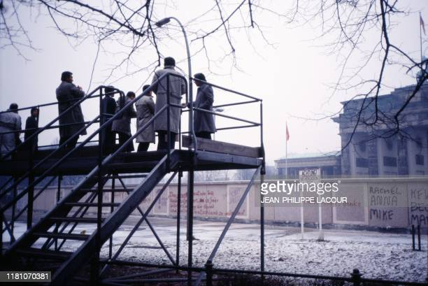 Picture taken in 1988 and made available on November 9, 2019 shows people standing on a platform in West Berlin and watching over the Berlin Wall...