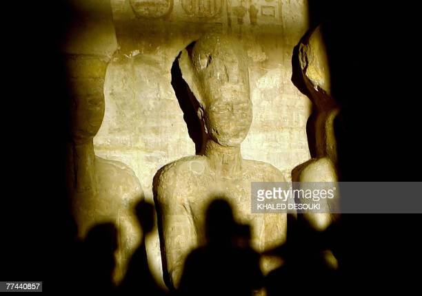 A picture taken in 2002 shows tourists casting their shadows as a ray of light illuminates the statue of Ramses II inside the temple of Abu Simbel...