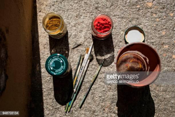 A picture taken in a Renaissance's mansion where he restores an ancient sundial on April 17 2018 in Saluzzo near Turin shows handmade colours used by...