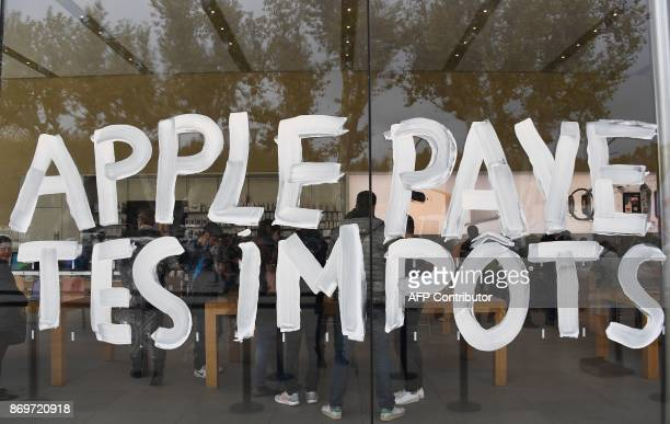 A picture taken in AixenProvence southern France on November 3 2017 shows the writing 'Apple pay your taxes' on the window of the Apple store during...