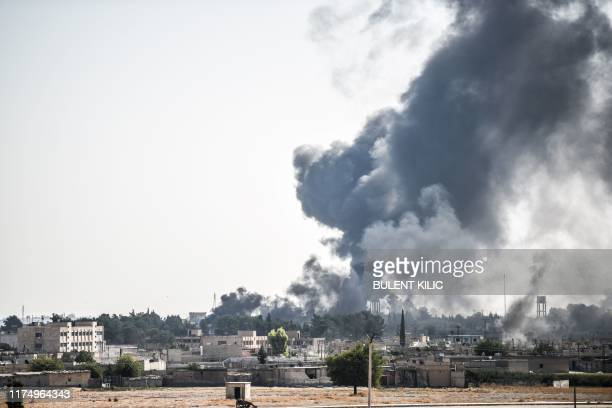 Picture taken in Akcakale at the Turkish border with Syria on October 10, 2019 shows smokes rising from the Syrian town of Tal Abyad after a mortar...
