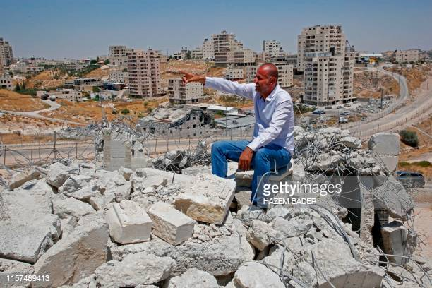 Picture taken in Dar Salah on July 24 shows Akram Zwahreh sitting on top of the rubble of his house during a tour for Fatah Movement to the site of...