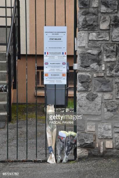 A picture taken in front of the Gendarmerie Nationale in Carcassonne on March 24 2018 shows flowers laid in tribute to the death of a gendarme killed...