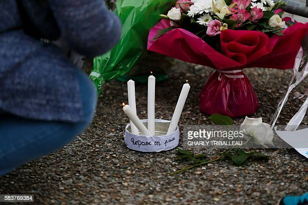 A picture taken in front of the SaintEtienne du Rouvray church on July 27 shows candels and a writing reading rest in peace at a make shift memorial...