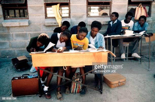 Picture taken in June 1984 of Zimbabwean students writing in an openair classroom of their primary school of Mtoko North East of Zimbabawe / AFP...