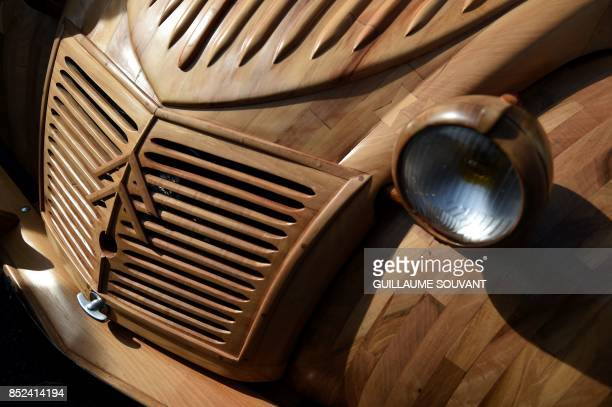 A picture taken in Loches Central France on September 23 2017 shows a detail of the wooden 2CV Citroen car built by French cabinetmaker Michel...