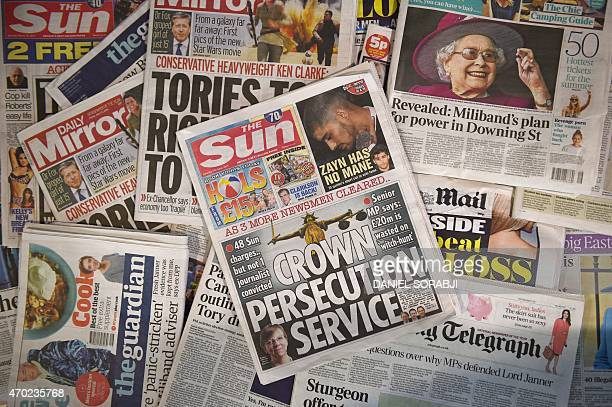 A picture taken in London on April 18 2015 shows an arrangement of British newspapers and an edition of the Sun newspaper carrying a front page story...