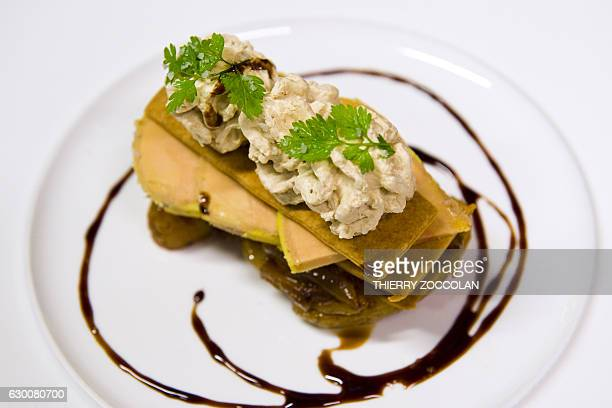 A picture taken in Maringues central France on December 8 2016 shows a millefeuille of potatos foie gras and black garlic prepared by Le Carroussel...