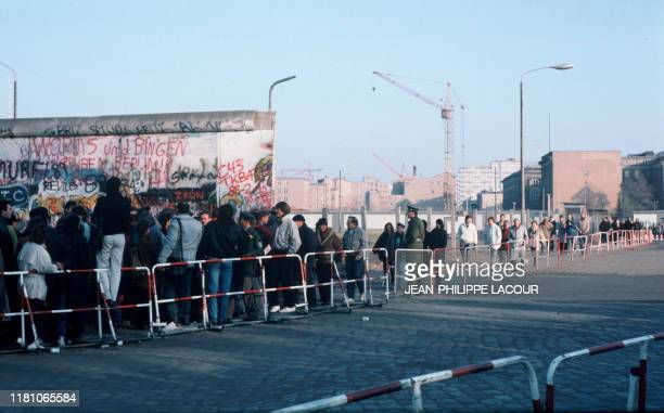 Picture taken in November 1989 and made available on November 9, 2019 shows people standing in front of remains of the Berlin Wall that separated...