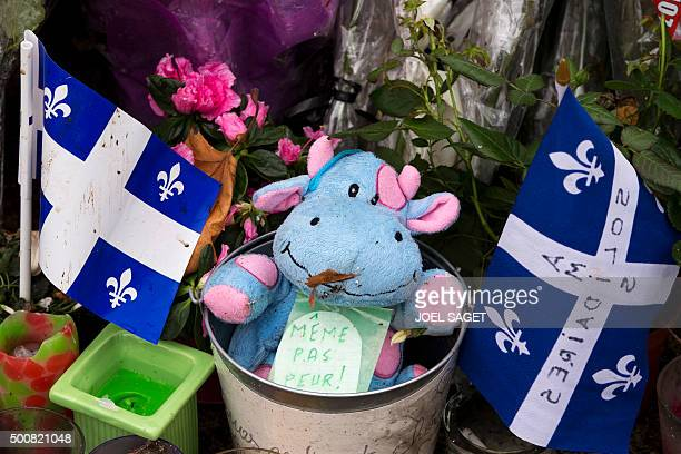 A picture taken in Paris on December 10 2015 shows a flag of Quebec next to a cuddly toy at a makeshift memorial in tribute to the victims of...