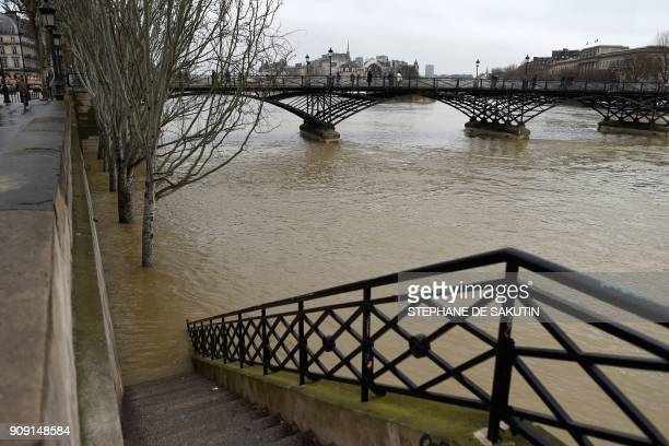 A picture taken in Paris on January 23 2018 shows a stair leading to a flooded bank and the Pont des Arts as the river Seine level has risen...