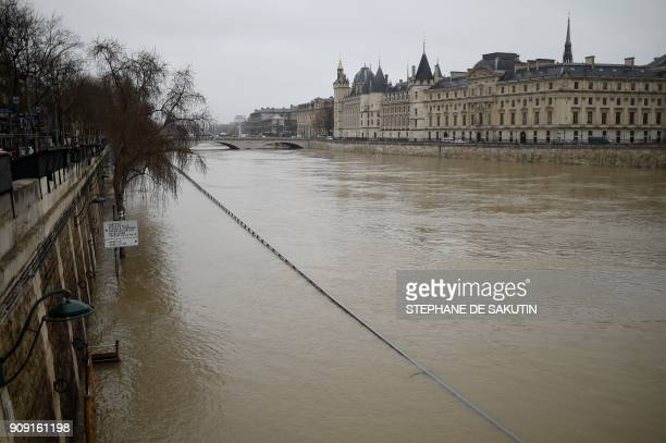 TOPSHOT A picture taken in Paris on January 23 2018 shows the Conciergerie and the banks flooded as the river Seine level has risen following...