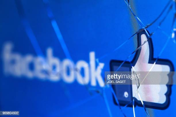 A picture taken in Paris on May 16 2018 shows the logo of the social network Facebook on a broken screen of a mobile phone