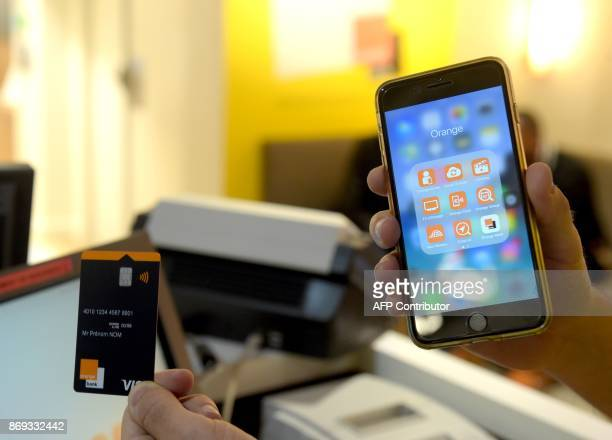 A picture taken in Paris shows an Orange credit card and an Orange Bank application on a smart phone as the Orange Bank online free banking service...