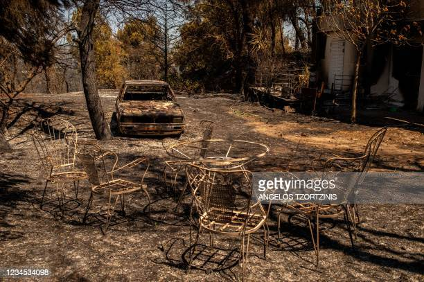 Picture taken in Pefkofito settlement, north of Athens, on August 7, 2021 shows a burnt car in a garden. - Hundreds of firefighters battled a blaze...