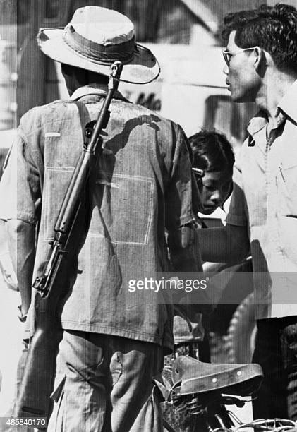A picture taken in Poipet close to the Thai border on April 18 shows a Khmer Rouge fighter with villagers after the garrison left and the guerrilla...