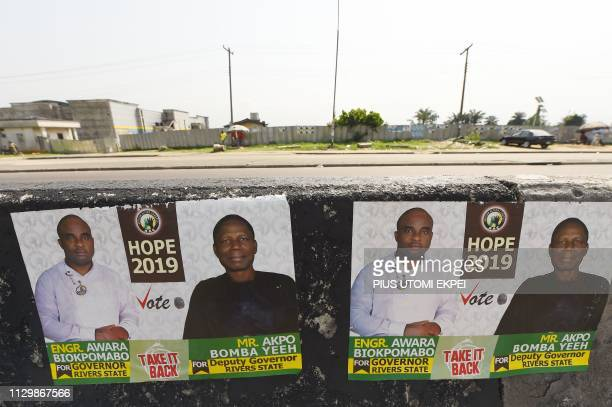A picture taken in Port Harcourt Rivers State on March 11 2019 shows campaign posters of gubernatorial candidate of African Action Congress Awara...