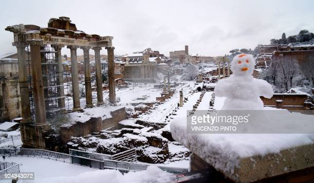 A picture taken in Rome on February 26 201 shows a view of the Ancient Forum and a snowman during a snowfall / AFP PHOTO / Vincenzo PINTO