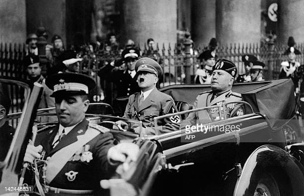 A picture taken in September 1937 in Munich shows German Chancellor Adolf Hitler riding in a car with Italian dictator Benito Mussolini while the...