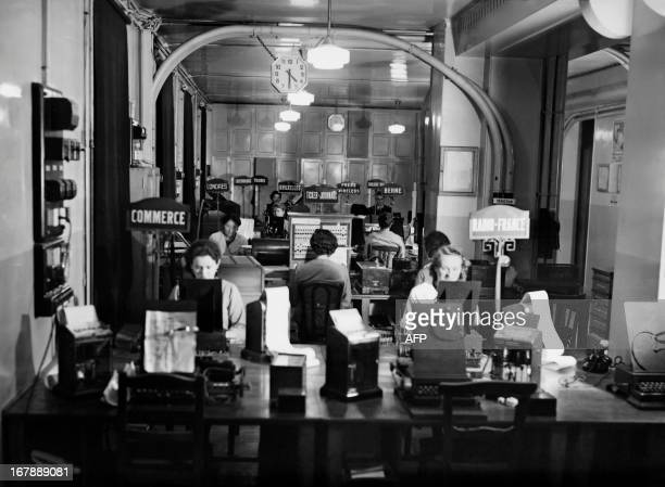 Picture taken in the 1930s in Paris, place de la Bourse, shows press employees working in a direct transmission office of the French news agency...
