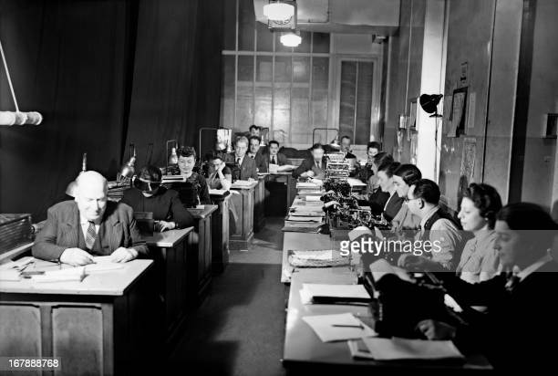 Picture taken in the 1930s in Paris, place de la Bourse, shows journalists working at a desk of the French news agency Havas. AFP PHOTO
