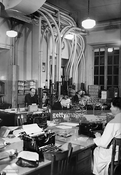Picture taken in the 1930s in Paris, place de la Bourse, shows journalists working at a desk of the French news agency Havas. In the background are...