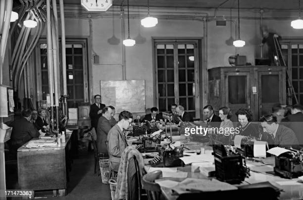 Picture taken in the 1930s in Paris, place de la Bourse, shows journalists working at a desk of the French news agency Havas. At left are pneumatic...