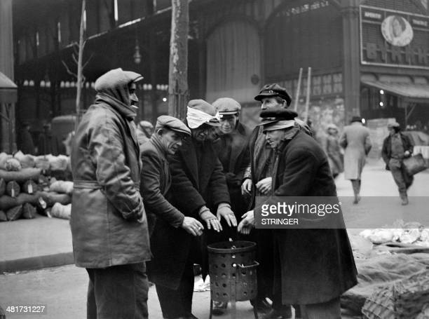 Picture taken in the 30s of freezing men warming up around a brazier during the season of winter in the street of the Les Halles district / AFP /...