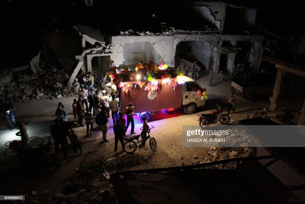 TOPSHOT - A picture taken in the early hours of June 25, 2017 shows Syrians gathered around an ice-cream vehicle amid destroyed buildings, on the last day of the fasting month of Ramadan in the rebel-held town of Douma, on the outskirts of the capital Damascus. PHOTO / Hamza Al-Ajweh