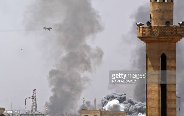 A picture taken in the Yarmuk Palestinian refugee camp in southern Damascus on April 27 2018 shows a Syrian air force Su22 fighter plane flying over...