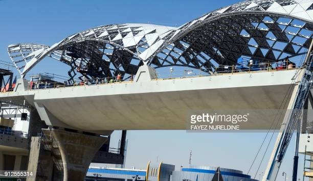A picture taken January 31 2018 shows foreign labourers working at a Riyadh metro station construction site on a suspended bridge in the Saudi capital