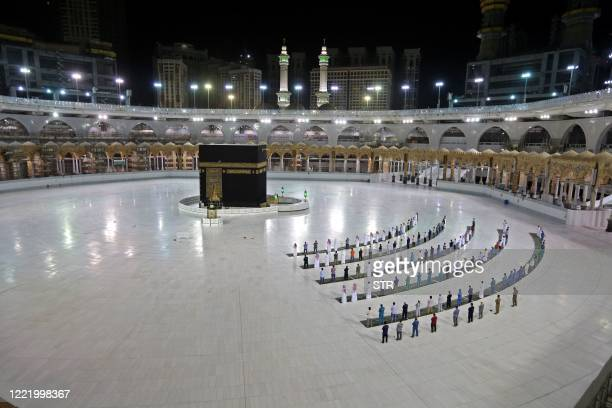 TOPSHOT A picture taken June 23 2020 shows a few worshippers performing alFajr prayer at the Kaaba Islam's holiest shrine at the Grand Mosque complex...