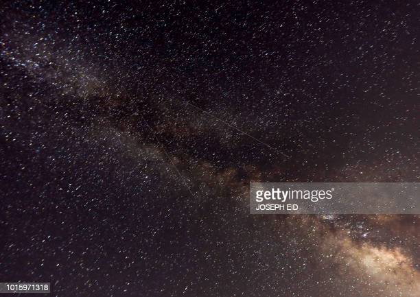 """Picture taken late on August 12, 2018 shows meteors crossing the night sky past the Milky Way during the annual """"Perseid"""" meteor show, in the..."""