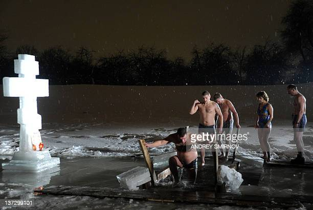 A picture taken late on January 18 shows Russian Orthodox church faithful gathering around a bath of ice cold water as they take turns plunging into...