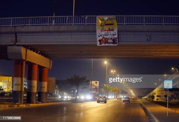 A picture taken late on November 3 2019 shows a poster on a bridge in the central Iraqi city of Najaf which reads Martyrs of the October Revolution...
