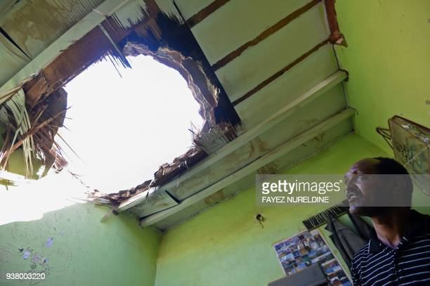 TOPSHOT A picture taken March 26 2018 in Um AlHammam district in Riyadh shows a man looking at a hole in a household cieling causes by falling...
