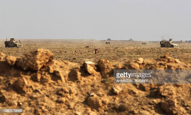 A picture taken near the Iraqi city of Qaim at the IraqiSyrian border on November 11 shows US Army vehicles patrolling the Syrian side of the border...