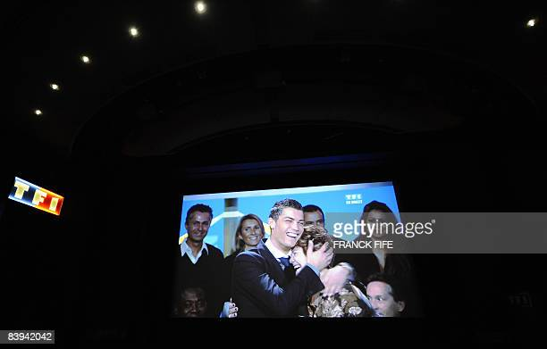 A picture taken of a TV screen shows Manchester United Portuguese winger Cristiano Ronaldo congratulated by his mother Maria Dolores dos Santos...