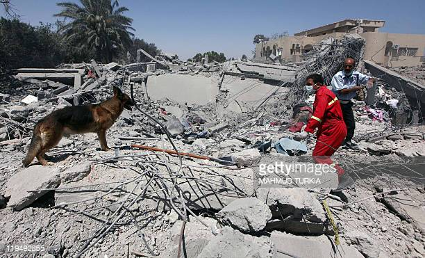 A picture taken on a governmentguided tour shows rescue teams inspecting on June 20 2011 damaged buildings on the sprawling estate of Khuwildi Hemidi...
