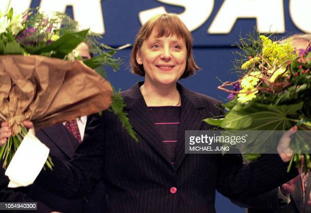 Picture taken on April 04 2000 shows Angela Merkel cheering with flowers after being elected as the new leader of Christian Democratic Union at a CDU...